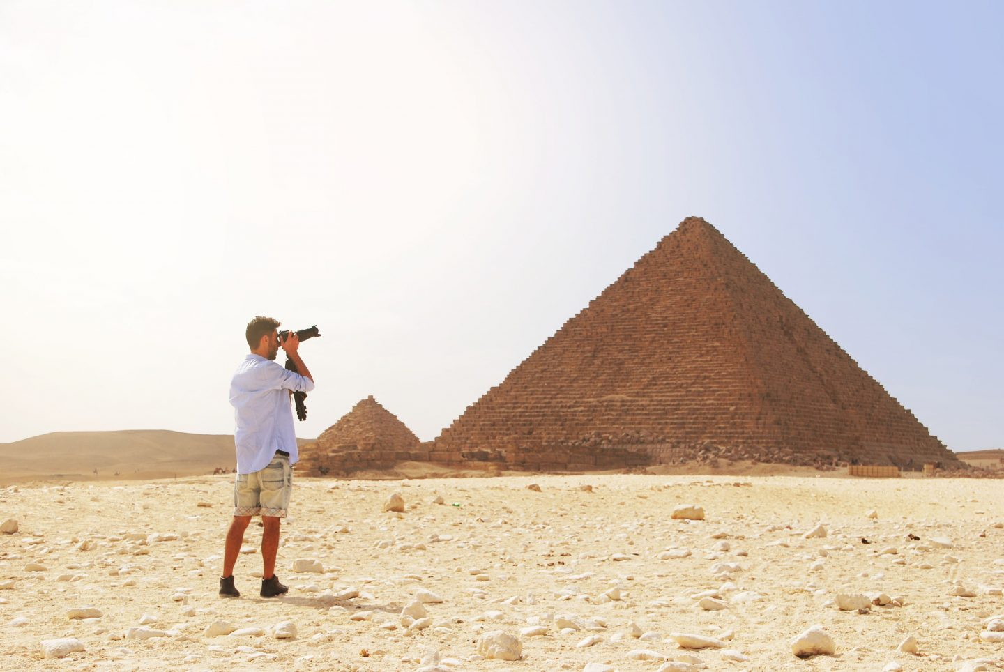 A man taking photograph of the pyramid of egypt. A must have egypt packing list